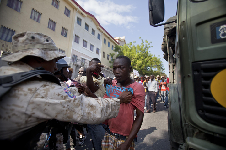 A protester is detained by police during a demonstration to demand the resignation of President Michel Martelly, in Port-au-Prince, Haiti. The protest was the latest in a series of demonstrations demanding Martelly leave office before his term expires next year. (Dieu Nalio Chery/AP Photo)