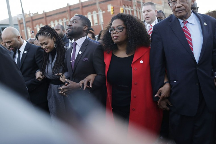 "Oprah Winfrey locks arms with David Oyelowo, left, who portrays Martin Luther King Jr. in the movie ""Selma,"" Ava DuVernay, the director of ""Selma"" and rapper Common, far left, as they march to the Edmund Pettus Bridge in honor of Martin Luther King Jr., Sunday, Jan. 18, 2015, in Selma, Ala. (AP Photo/Brynn Anderson)"