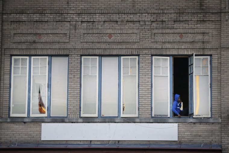 A spectator watches out his window as marchers make their way to the Edmund Pettus Bridge in honor of Martin Luther King Jr.,Sunday, Jan. 18, 2015, in Selma, Ala. (AP Photo/Brynn Anderson)