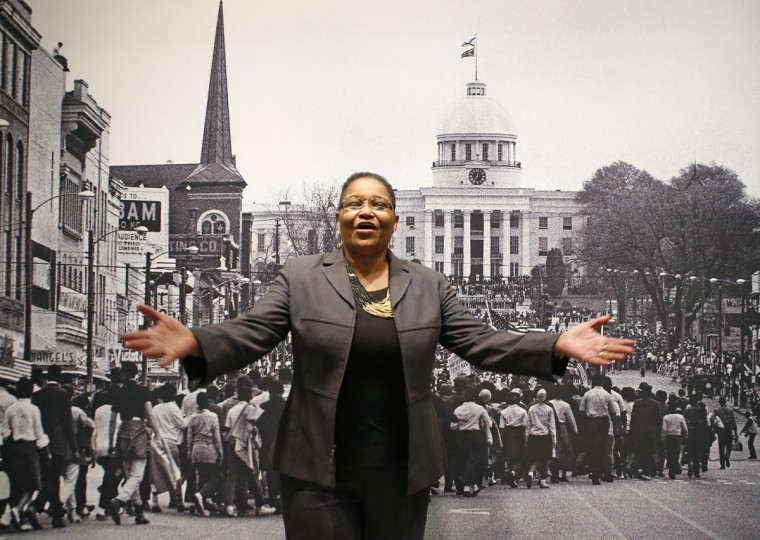 "Lynda Blackmon Lowery speaks during a Martin Luther King Day appearance at the New York Historical Society in New York, Sunday, Jan. 18, 2015, told of her experiences as the youngest participant in the 1965 march from Selma to Montgomery, Alabama demanding voting rights for African-Americans, detailed in her memoir ""Turning 15 on the Road to Freedom,"" co-witten with Elspeth Leacock and Susan Buckley. Lowery stands in front of a Stephen Somerstein photograph of the march, on view at the museum. (AP Photo/Kathy Willens)"