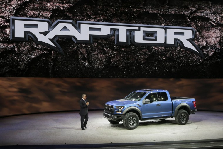 Ford Executive Vice President and President, The Americas, Joe Hinrichs, stands next to th Ford Raptor during the North American International Auto Show, Monday, Jan. 12, 2015 in Detroit. (AP Photo/Carlos Osorio)