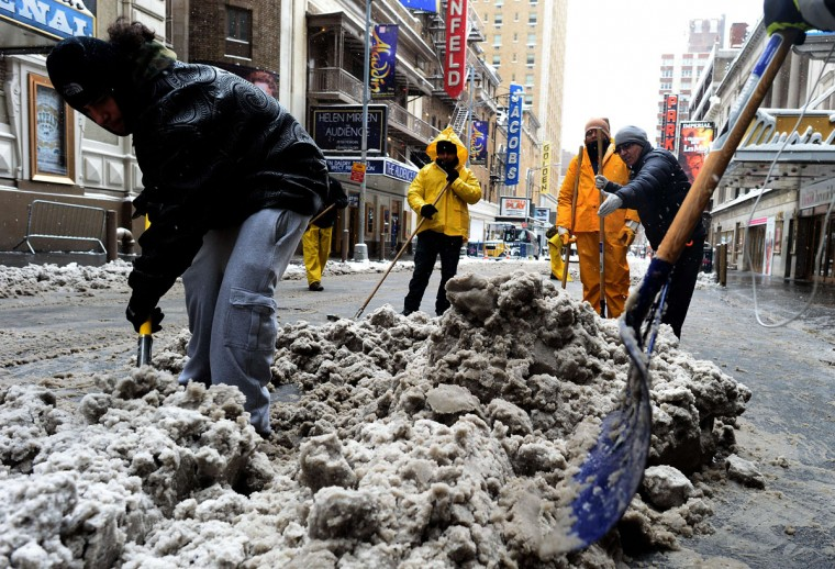 Workers shovel snow off a nearly deserted street in New York's Times Square what is normally a crowed morning rush hour after a snowstorm on January 27, 2015. (JEWEL SAMAD/AFP/Getty Images)