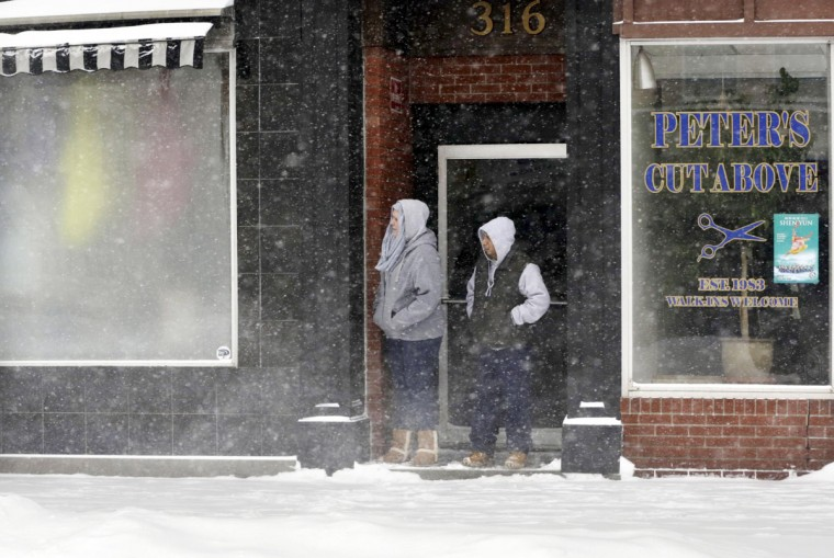 People take cover in a doorway, Tuesday, Jan. 27, 2015, in Pittsfield, Mass., after a winter storm roared up the East Coast. (AP Photo/The Berkshire Eagle, Stephanie Zollshan)