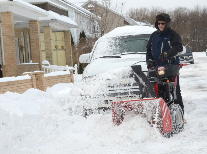 Jerry Jackson operates his snow blower Tuesday, Jan. 27, 2015, in front of his neighbor's home in Kelayres, Pa., as he cleans up snow that fell in northeast Pennsylvania. (AP Photo/Hazleton Standard-Speaker, Eric Conover)