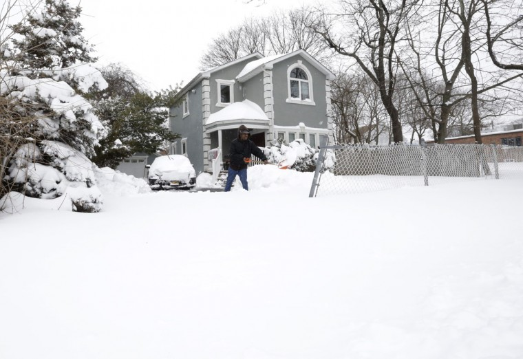 Darryl Thompson shovels his driveway, Tuesday, Jan. 27, 2015 in Central Islip, N.Y. (AP Photo/Mary Altaffer)
