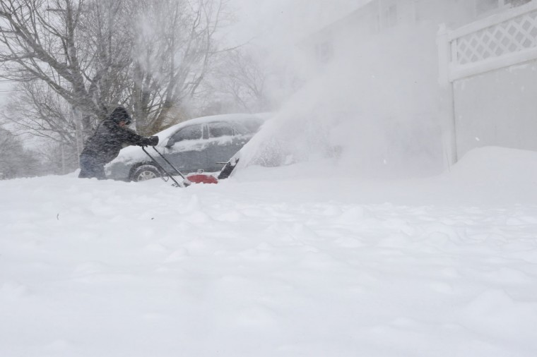 Alejandro Buruca clears snow from his driveway, Tuesday, Jan. 27, 2015 in Central Islip, N.Y. (AP Photo/Mary Altaffer)