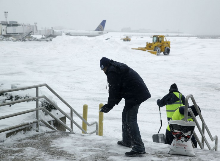 Men and machines clear snow off the tarmac at LaGuardia Airport in New York, Tuesday, Jan. 27, 2015. (AP Photo/Seth Wenig)