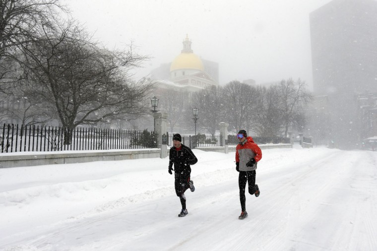 Runners race down Beacon Street in front of the Massachusetts Statehouse, rear, during a winter snowstorm Tuesday, Jan. 27, 2015, in Boston. (AP Photo/Steven Senne)