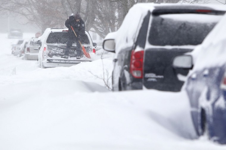 Peter Nieuwenhuizen digs his truck out as he prepares to drive to work in Norfolk, Mass., on Tuesday, Jan. 27, 2015. (AP Photo/Standard Times, Peter Pereira)