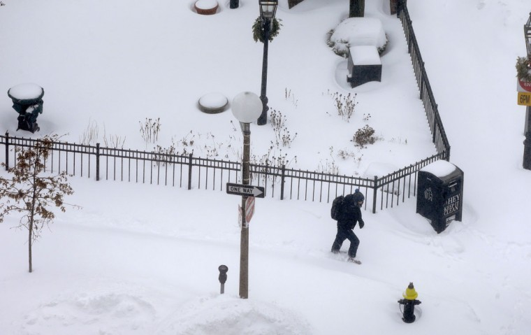A pedestrian walks along a snow-covered sidewalk during a winter snowstorm Tuesday, Jan. 27, 2015, in Boston. (AP Photo/Steven Senne)