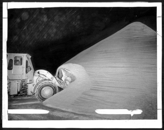 """March 20, 1977: A front-end loader takes a bite out of a mountain of """"raw"""" cane sugar in a storage shed at the refinery. Photo by Walter. M. McCardell."""