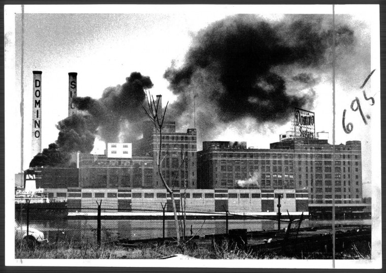 """March 12, 1974: How sweet it isn't -- What appears to be clouds of black smoke emitting from Domino Sugar is in reality being spewed by the freighter """"Union Defenders."""" Photo by Lloyd Pearson."""
