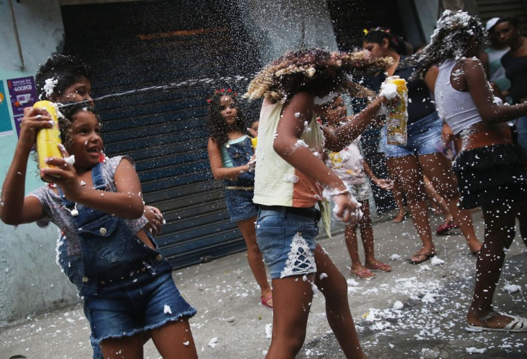 Young revelers spray foam during a 'bloco' street parade in the Port Zone during pre-Carnival festivities on January 24, 2015 in Rio de Janeiro, Brazil. Carnival officially starts February 13 but pre-Carnival festivities are already underway in Brazil. (Photo by Mario Tama/Getty Images)