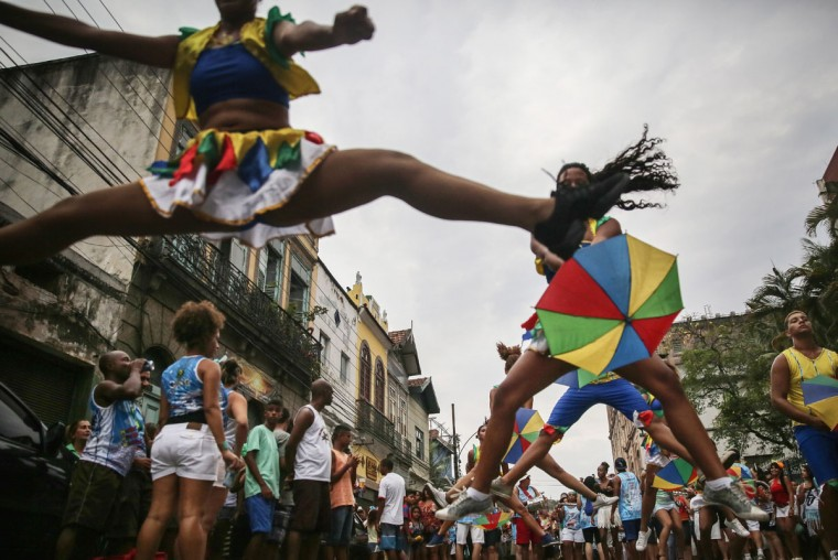 Revelers dance during a 'bloco' street parade in the Port Zone during pre-Carnival festivities on January 24, 2015 in Rio de Janeiro, Brazil. Carnival officially starts February 13 but pre-Carnival festivities are already underway in Brazil. (Photo by Mario Tama/Getty Images)