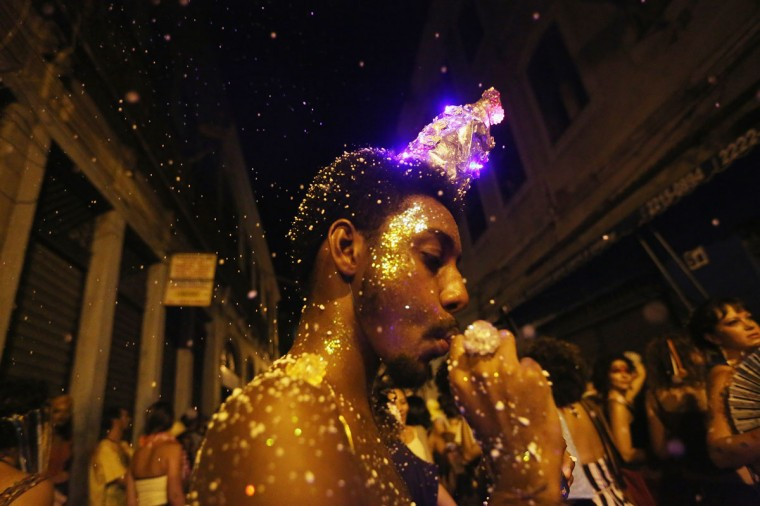 Sprayed foam floats down over a reveler during the My Light is LED 'bloco' pre-Carnival street parade on February 12, 2015 in Rio de Janeiro, Brazil. Carnival runs this year February 13-17. (Photo by Mario Tama/Getty Images)