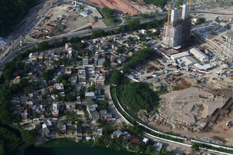 Construction continues (R) at the Olympic Park for the Rio 2016 Olympic Games in the Barra da Tijuca neighborhood, as remaining homes from the Vila Autodromo favela stand (L) on February 24, 2015 in Rio de Janeiro, Brazil. The Olympic Park will occupy 1.18 million square meters hosting 16 Olympic disciplines and will be the heart of the games. (Photo by Mario Tama/Getty Images)