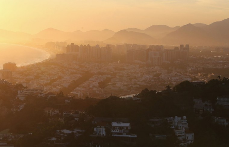 The sun begins to set over the Barra da Tijuca neighborhood (C), which will host the primary venue cluster for the Rio 2016 Olympic Games, on February 24, 2015 in Rio de Janeiro, Brazil. The city of Rio continues to prepare to host the upcoming Olympic Games which kickoff on August 5, 2016. (Photo by Mario Tama/Getty Images)