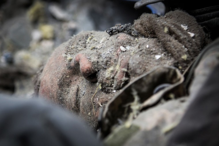 A dead Ukrainian soldier lies amongst the wreckage of the destroyed Donetsk airport after being recovered by Ukrainian soldier prisoners-of-war who were forced to search through the wreckage by pro-Russian rebels on February 26, 2015 in Donetsk, Ukraine. The Donetsk airport has been one of the most heavily fought over pieces of land between the Ukrainian army and pro-Russian rebels. (Photo by Andrew Burton/Getty Images)