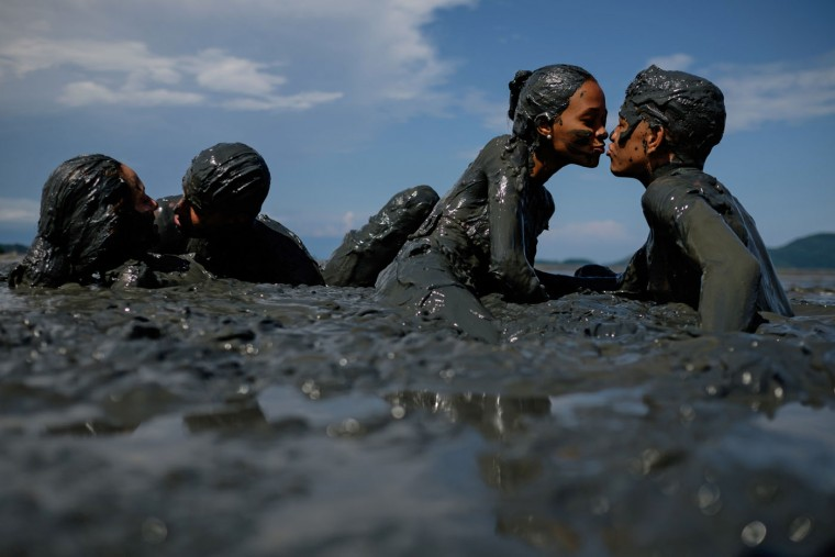 "Couples kiss as they prepare for ""Bloco da Lama,"" a mud carnival in Paraty, about 250km south of Rio de Janeiro, Brazil, on February 14, 2015. ""Bloco da Lama"" was started in 1986 by two teenagers playing with mud. Yasuyoshi Chiba/AFP/Getty Images"