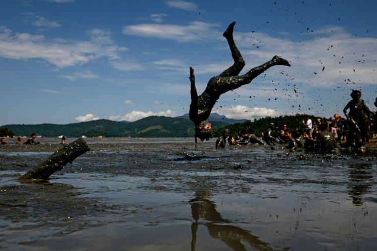 "A reveller dives to prepare for ""Bloco da Lama,"" a mud carnival in Paraty, about 250km south of Rio de Janeiro, Brazil, on February 14, 2015. ""Bloco da Lama"" was started in 1986 by two teenagers playing with mud. Yasuyoshi Chiba/AFP/Getty Images"