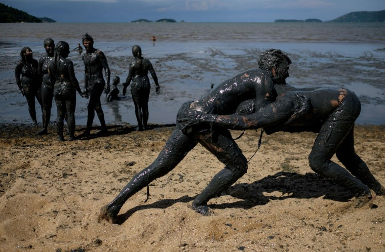 "Revellers play after covering their bodies with mud ahead of ""Bloco da Lama"" a mud carnival in Paraty, about 250km south of Rio de Janeiro, Brazil, on February 14, 2015. ""Bloco da Lama"" was started in 1986 by two teenagers playing with mud. Yasuyoshi Chiba/AFP/Getty Images"