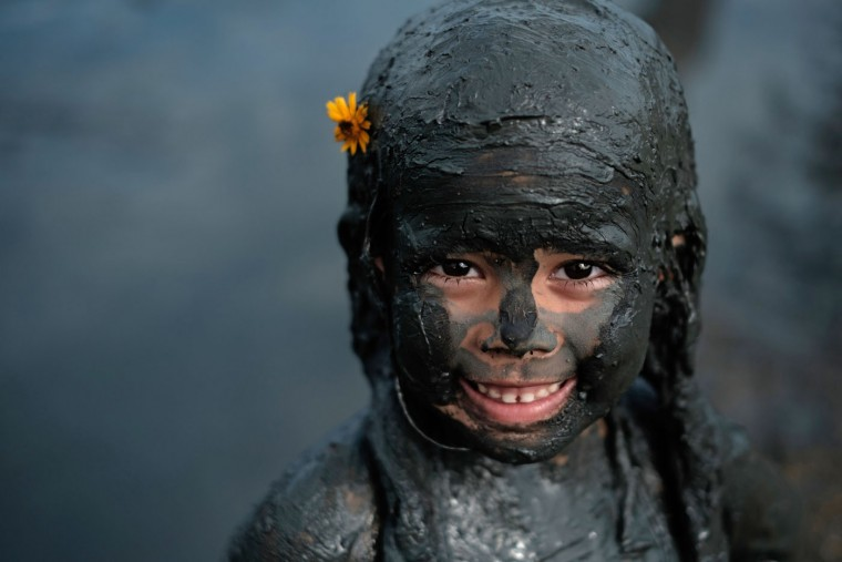 "A girl prepares for ""Bloco da Lama,"" a mud carnival in Paraty, about 250km south of Rio de Janeiro, Brazil, on February 14, 2015. ""Bloco da Lama"" was started in 1986 by two teenagers playing with mud. Yasuyoshi Chiba/AFP/Getty Images"