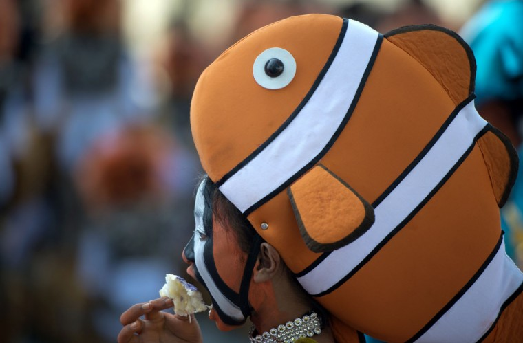 A student wearing a fish costume eats bread as she waits to dance during the annual Caracol Festival in Manila on February 22, 2015. Participants of the Caracol Festival dress in different costumes of wildlife and endangered species to express the need to preserve Manila's environment and cultural heritage. (Noel Celis/AFP/Getty Images)