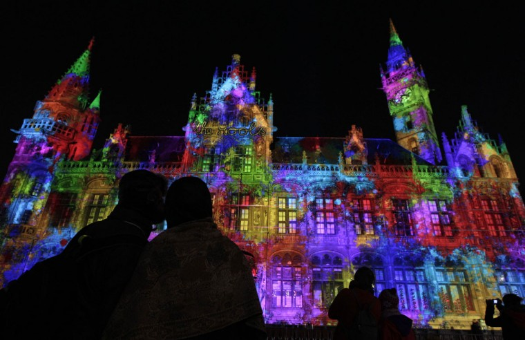 A couple watches a light projection on the former post office during the 'Light Festival' in Ghent, Belgium, Friday, Jan. 28, 2011. The light Festival evokes an exploratory voyage along the medieval city of Ghent by unexpected projections on buildings. (AP Photo/Yves Logghe)