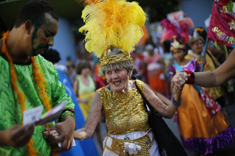 """An elderly patient in costume from the Nise de Silveira mental health institute dances during the institute's carnival parade, coined in Portuguese: """"Loucura Suburbana,"""" or Suburban Madness, in the streets of Rio de Janeiro, Brazil, Thursday, Feb. 12, 2015. Patients, their relatives and institute employees held their parade one day before the official start of Carnival. (AP Photo/Silvia Izquierdo)"""
