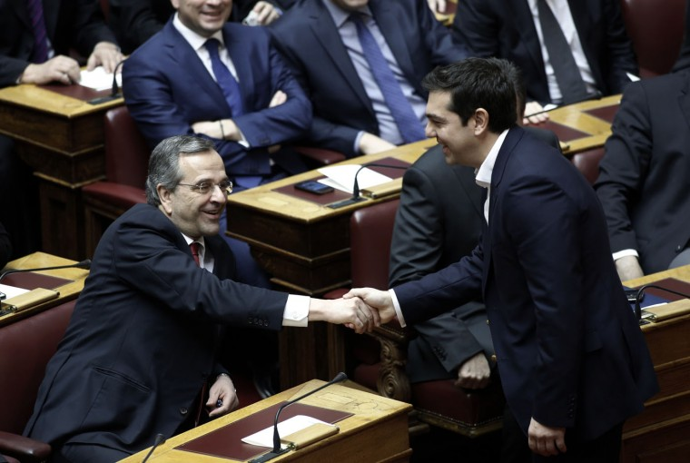 Greece's Prime Minister Alexis Tsipras, right, shakes hands with former Prime Minister and leader of New Democracy conservative party Antonis Samaras during swearing in ceremony at the first convention of the Parliament since the Jan. 25 elections in Athens on Thursday, Feb. 5, 2015. Non Greek Orthodox lawmakers were sworn in with a secular, or Muslim version of the oath. Jittery investors dumped Greek shares Thursday after the European Central Bank tightened the screws on the country's banking system, piling pressure on the new anti-austerity government to seek a compromise with bailout creditors. (AP Photo/Yannis Kolesidis, Pool)