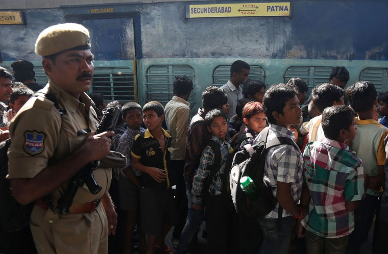 Indian rescued child laborers stand in a queue to board a train to be reunited with their parents in Bihar, one of India's poorest states, at a railway station in Hyderabad, India, Thursday, Feb. 5, 2015. Police have rescued hundreds of children working in hazardous industries in a southern Indian city despite laws that ban child labor. In a series of raids on leather tanning and plastic factories in Hyderabad over the past 10 days, police rescued at least 350 children. (AP Photo/Mahesh Kumar A.)