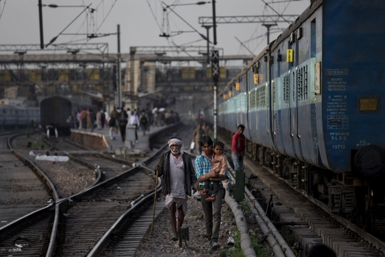 Indian commuters walk between rail tracks in New Delhi, India, Thursday, Feb. 26, 2015. The railways budget unveiled Thursday by Railway Minister Suresh Prabhu envisions $137 billion being invested over the next five years to modernize trains and stations, improve safety and sanitation and expand the reach of the rails in the system that serves more than 23 million passengers a day. (Bernat Armangue/AP Photo)