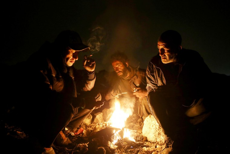 In this Wednesday, Feb. 11, 2015 photo, drug addicts gather around fire to warm themselves, in a suburb of Tehran, Iran. Anti-narcotics and medical officials say more than 2.2 million of Iran's 80 million citizens already are addicted to illegal drugs, including 1.3 million on registered treatment programs. They say the numbers keep rising annually, even though use of the death penalty against convicted smugglers has increased, too, and now accounts for more than nine of every 10 executions. (Ebrahim Noroozi/AP)
