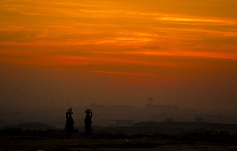 Pakistani nomad women carry water to their houses at dusk in Islamabad, Pakistan, Thursday, Feb 12, 2015. People living in suburbs of the capital are lacking basic necessities of life. (B.K. Bangash/AP)