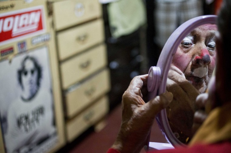 """Veteran clown Ricardo Farfan, popularly known as """"Pitito,"""" paints his face as he prepares for his 91st birthday party at his home in Lima, Peru. Farfan, who started working at his father's circus in 1927 when he was three-years-old, still works sporadically as a clown at private parties and says his children wish he would retire. He said he does it for the joy of practicing his craft and will do so until he dies. (AP Photo/Esteban Felix)"""