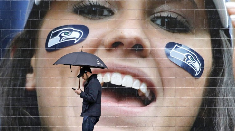 A pedestrian walks past a large photo of a cheering Seattle Seahawks' fan outside the team's NFL football stadium Tuesday, Feb. 3, 2015, in Seattle. The grief, anger and bewilderment felt by many Seahawks fans after the team's loss to the New England Patriots in the Super Bowl shows little sign of abating, even days later. (AP Photo/Elaine Thompson)