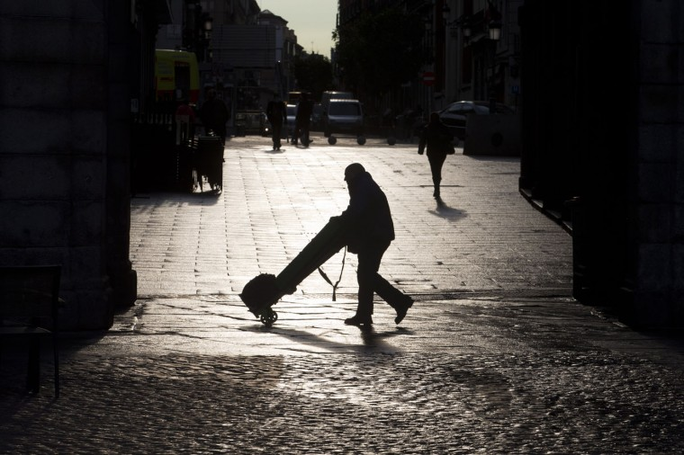A man pushes a barrow in Madrid, Spain, Thursday, Feb. 26, 2015 as the day gets underway in the Spanish capital. (Paul White/AP Photo)