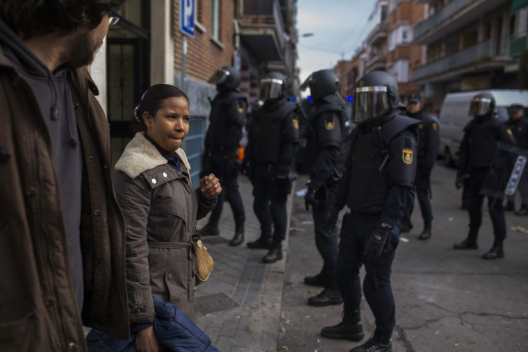 Elvira Reyes Mariano, centre left, leaves the apartment after she got evicted by riot police in Madrid, Spain, Thursday, Feb. 12, 2015. The landlord's loss of the apartment to Bankia bank is causing Reyes Mariano and her family's eviction. Reyes Mariano lives with her husband Soltero Rodriguez Cuevas, 44 years old, both unemployed, her sister and their three kids. They continued to occupy a foreclosed Bankia bank apartment after their landlord left as they could not afford to pay rent. Dozens of housing right activists tried to stop the process by blocking the building entrance but riot police removed them and evicted the family. (Andres Kudacki/AP)