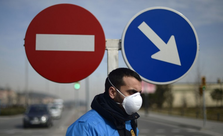 A policeman wearing a mask blocks the entrance to the area after a chemical explosion in Igualada, Spain, Thursday, Feb. 12, 2015. Spanish authorities Thursday ordered the residents of five northeastern towns to stay indoors for some two hours after a chemical explosion at a warehouse spread a large, orange toxic cloud over the area. A spokeswoman for Catalonia's regional firefighting department said the blast occurred when products being delivered to a warehouse in the city of Igualada became mixed, exploded and set a truck on fire. She said two people were slightly injured. Firefighters said the chemicals were nitric acid and ferric chloride. The region's Civil Protection department ordered some 65,000 residents of Igualada and four nearby towns to stay indoors until the cloud dissipated. The order was lifted two hours later but maintained for pregnant women, children, elderly people and those with respiratory problems. (Manu Fernandez/AP)