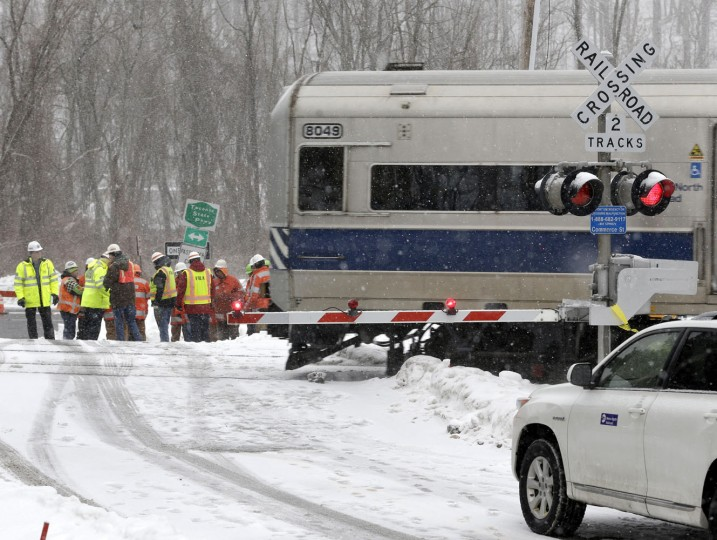 A Metro-North Railroad train passes through the intersection that was the site of a fatal collision between an SUV and a commuter train in Valhalla, N.Y., Thursday, Feb. 5, 2015. An investigation into what caused a fiery crash that killed a motorist and five rail riders is focusing on how a mother of three described by friends as safety conscious ended up between two crossing gates in her SUV as a commuter train barreled toward her. (AP Photo/Seth Wenig)