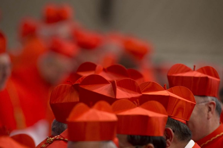 Cardinals wearing their red three-cornered biretta hats gather during a ceremony in St. Peter's Basilica at the Vatican. Pope Francis welcomed 20 new cardinals Saturday into the elite club of churchmen who will elect his successor and immediately delivered a tough-love message to them, telling them to put aside their pride, jealousy and self-interests and instead exercise perfect charity. AP Photo/Andrew Medichini