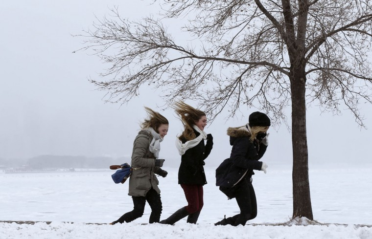 Three young women make their way in a stiff wind to the Adler Planetarium as lake effect snow obscure a favorite panoramic view of Chicago's skyline, Thursday, Feb. 26, 2015, in Chicago. (Charles Rex Arbogast/AP Photo)