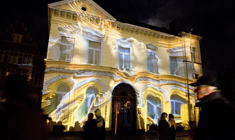 Visitors look at a light projection on a house during the light festival in Ghent, Belgium, on Sunday, Feb. 1, 2015. More than 40 light installations are on display during the festival, which takes places every three years. (AP Photo/Virginia Mayo)