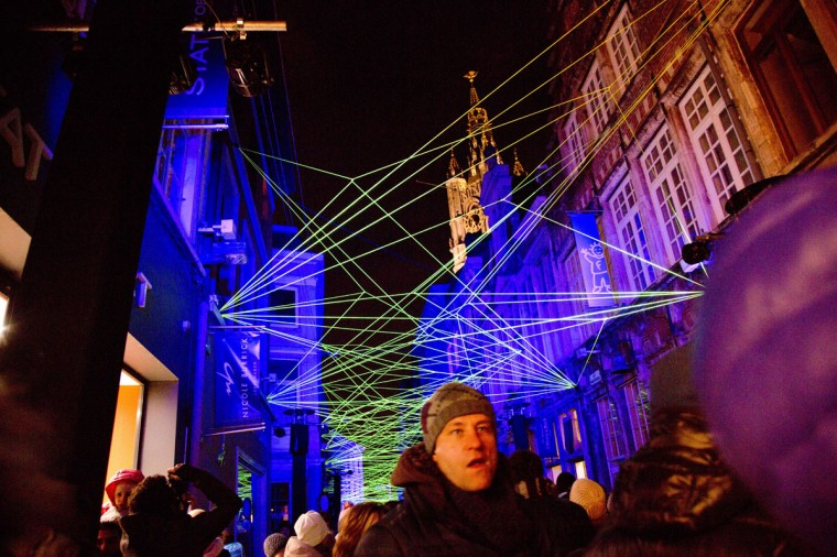 Visitors walk down an alley with a light projection display during the light festival in Ghent, Belgium on Sunday, Feb. 1, 2015. More than 40 light installations were on display during the festival, which takes places every three years. (AP Photo/Virginia Mayo)