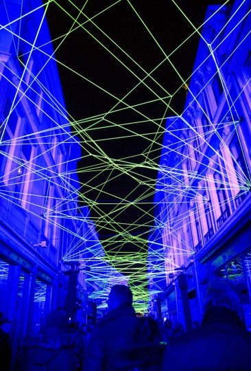 Visitors walk down an alley with a light projection during the light festival in Ghent, Belgium, on Sunday, Feb. 1, 2015. More than 40 light installations were on display during the festival, which takes places every three years. (AP Photo/Virginia Mayo)