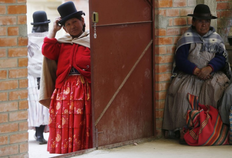 In this Feb. 4, 2105 photo, Aymara indigenous women watches elderly Aymara women warm up to play handball in El Alto, Bolivia. The games the grandmothers participate in are part of a program that El Alto sponsors to encourage older people to stay healthy by remaining active. (AP Photo/Juan Karita)