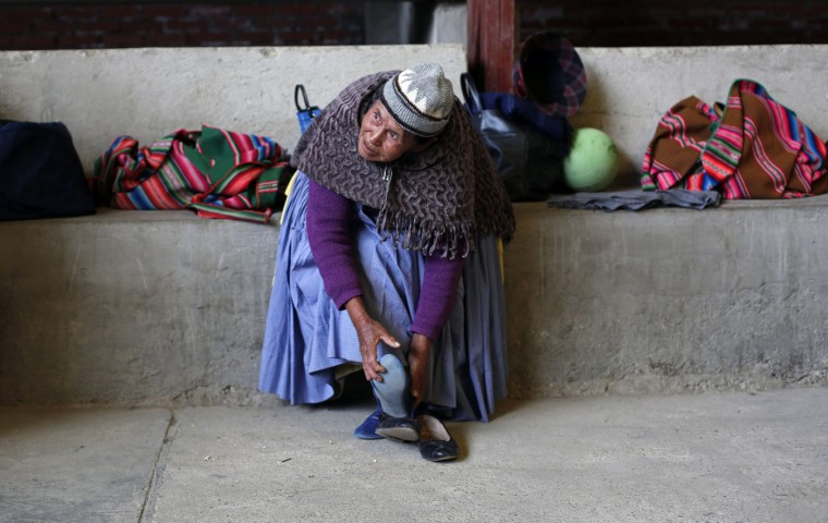 In this Jan. 28, 2105 photo, elderly Aymara indigenous woman Rosa Barco removes her sneakers after playing handball with fellow seniors in El Alto, Bolivia. The women, some of them great-grandmothers, arrive with their tennis shoes once a week, part of a program that the city sponsors to encourage older people to stay healthy by remaining active. (AP Photo/Juan Karita)