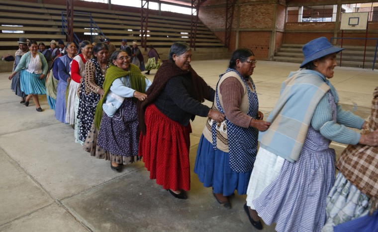 "In this Jan. 28, 2105 photo, elderly Aymara indigenous women hold on to each other as they run laps to warm up for a handball game in El Alto, Bolivia. The grandmothers, known in the Aymara language as ìAwichas,"" warm-up with exercises while singing a childhood song. (AP Photo/Juan Karita)"