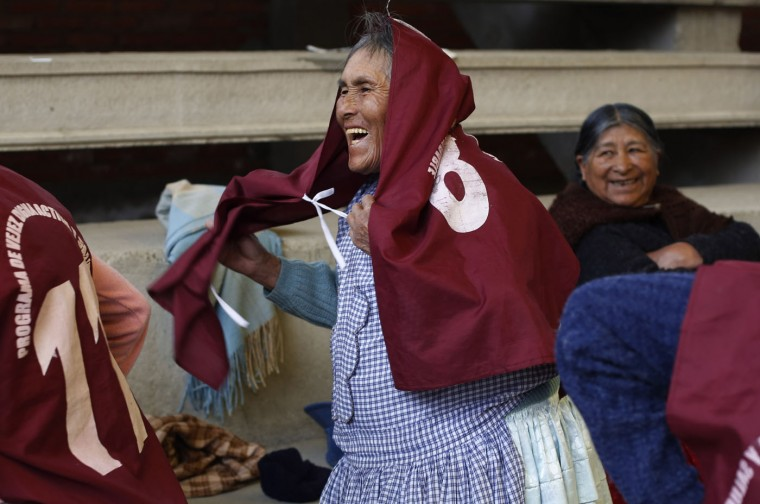 "In this Jan. 28, 2105 photo, 83-year-old Josefina Tito slips a jersey over her dress as she prepares for a handball game with fellow Aymara indigenous elderly women in El Alto, Bolivia. Tito said she's been playing handball for nine years, and that she also plays other sports with her son at home. ""I'm always playing"" she said. (AP Photo/Juan Karita)"