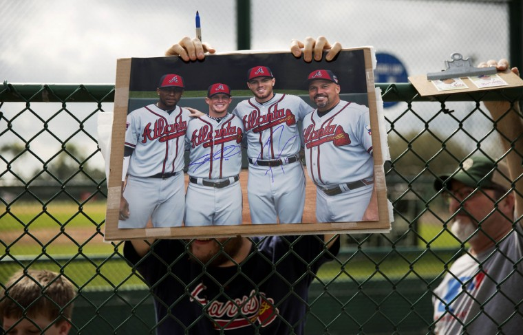 A fan holds a photo over a fence of Atlanta Braves' Julio Teheran, from left, Craig Kimbrel, Freddie Freeman and manager Fredi Gonzalez while waiting for Teheran's autograph as he passes by during a spring training baseball workout, Monday, Feb. 23, 2015, in Kissimmee, Fla. (AP Photo/David Goldman)